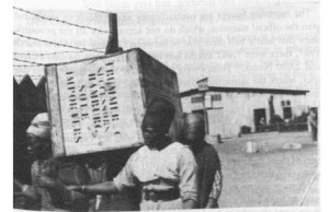 Herero women unloading a crate, Swakopmund, 1905. Likely detainees in the Swakopmund concentration camp. NAN 5041